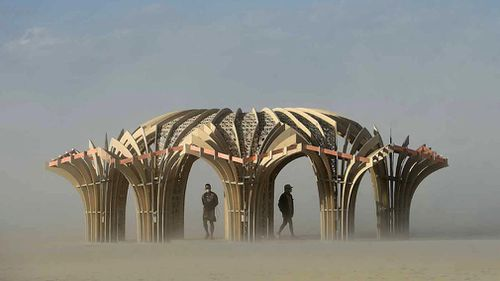 """""""Burners"""" stand inside an art sculpture during a dust storm at Burning Man. (AP)"""