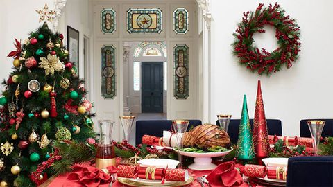 Christmas set up with Christmas tree and wreath, table with Christmas crackers and roast ham