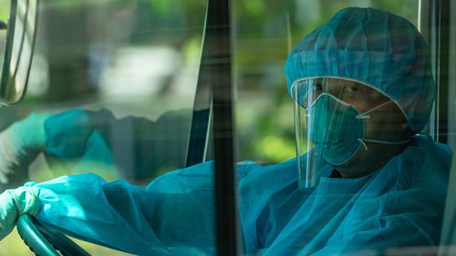 A driver wearing PPE stands by in a minibus as residents are evacuated from a nursing home to a quarantine center after multiple infections of the COVID-19 on July 24, 2020 in Hong Kong, China.