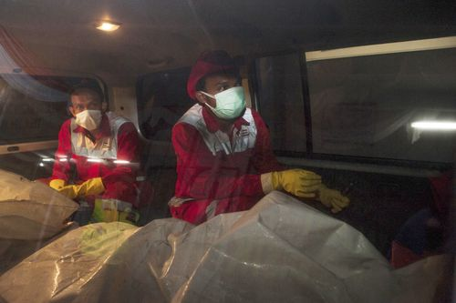 Rescue personnel accompany body bags to the hospital.