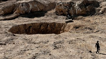 A member of the Hashed al-Shaabi (Popular Mobilisation) paramilitaries walks next to a sinkhole in the village of Athbah, south of Mosul. (AFP)
