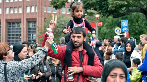 A woman gives a cuddly toy to an arriving refugee in Dortmund. (AAP)