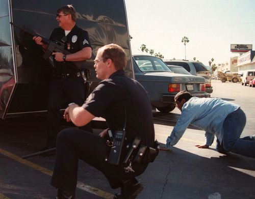 Los Angeles Police and a civilian take cover as bank robbers are confronted at a Bank of America in North Hollywood, Los Angeles.