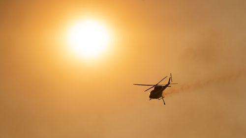 A water-bombing helicopter over Mount Tennant as the fire front of the Orroral Valley fire creeps through the Namadgi National Park on January 30, 2020 in Canberra, Australia.