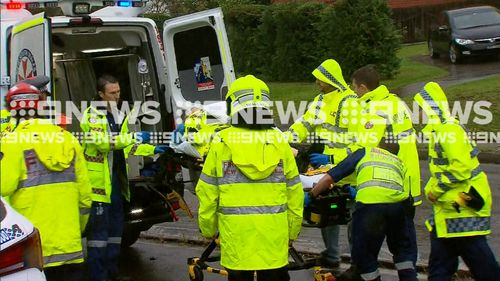 Emergency services load the injured police officer into an ambulance.