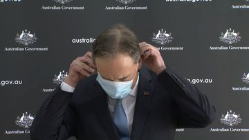Health Minister struggles with face mask while addressing outbreak