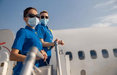 Flight attendants boarding plane wearing coronavirus face mask