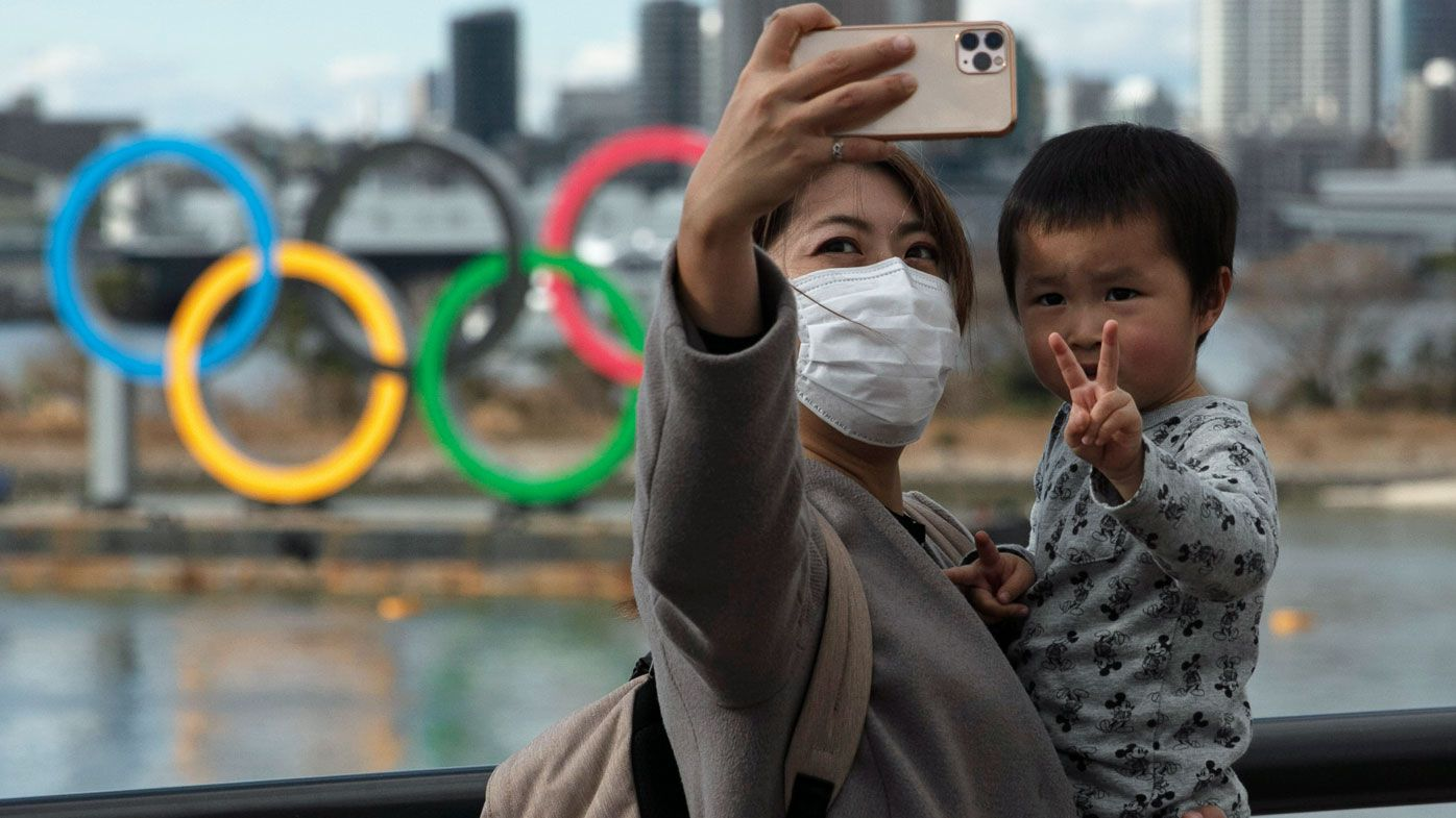 A woman with a young boy takes a selfie with the Olympic rings, in Tokyo's Odaiba district.