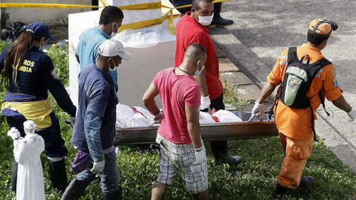 Rescue workers carry a landslide victim on a stretcher. (AAP)