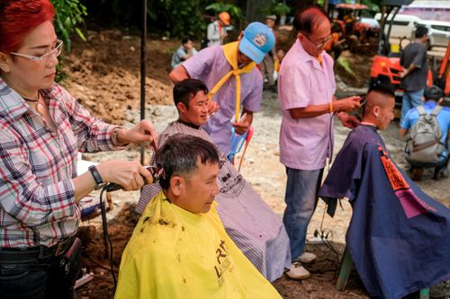 Rescuers and family members get free hair cuts from volunteer barbers at the makeshift camp above the cave. Picture: Getty