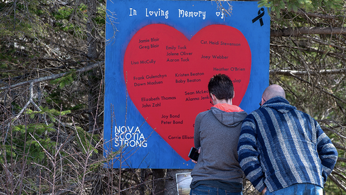 People pay their respects at a roadside memorial in Portapique, Nova Scotia on Sunday, April 26, 2020. A man went on a murder rampage in Portapique and several other Nova Scotia communities killing 22 people. (Andrew Vaughan/The Canadian Press via AP)