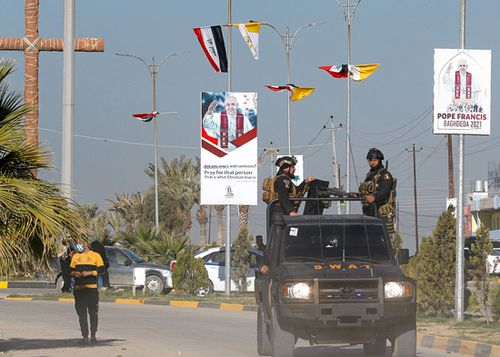 Iraqi security forces pass by Iraqi and Vatican flags and posters in a street in Qaraqosh, Iraq, Monday, Feb. 22, 2021, announcing the visit of the Pope Francis.