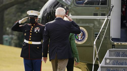 President Joe Biden salutes before boarding Marine One with first lady Jill Biden at the White House in Washington, Friday, Feb. 26, 2021, for a short trip to Andrews Air Force Base, Md., and then on to Houston