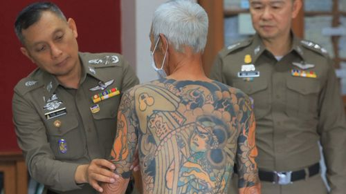 Mr Shirai's intricate tattoos were spotted in a photo of him sitting at a checkers table in August 2017, which ultimately led to his arrest (AP).