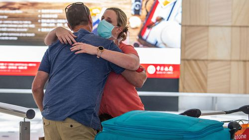 A husband and wife embrace after she arrived from flight QF66 from Johannesberg wearing protective a face mask at Sydney International Airport, Sydney, Friday, March 27, 2020