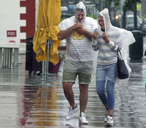 Tourists brave the elements as heavy rains bucket down on Miami.