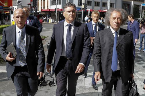 Dreamworld CEO Craig Davidson (centre) arrives with lawyers to the pre-inquest hearing into the fatal accident at the Dreamworld theme park, at the Brisbane Coroners Court in Brisbane, Tuesday, April 3, 2018.