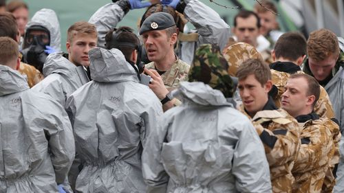 Soldiers in protective gear investigate
