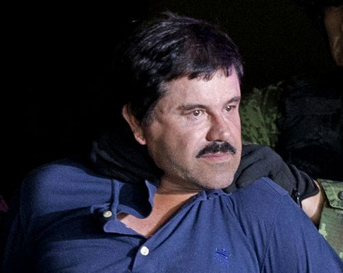 """In this Jan. 8, 2016 file photo, a handcuffed Joaquin """"El Chapo"""" Guzman is made to face the press as he is escorted to a helicopter by Mexican soldiers and marines at a federal hangar in Mexico City. Guzman is scheduled to appear in person in a federal court in New York. A judge initially ruled that Guzman would appear in court by video on Friday, Feb. 3, rather than have marshals escort him to and from a high-security Manhattan jail cell. The order was changed after his lawyers asked the judge to reconsider. (AP Photo/Eduardo Verdugo, File)"""