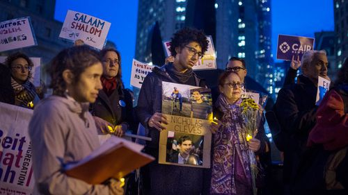 Bahij Chancey, 26, center, holds a photo of his friend and, one of the victims Nicholas Cleves, during an interfaith vigil for peace at Foley Square. (AAP)