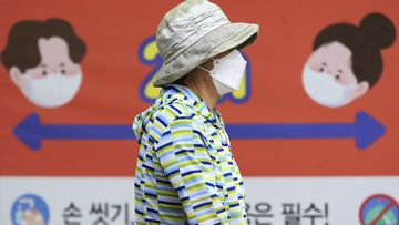 A woman wearing a face mask to help protect against the spread of the new coronavirus passes by a banner about precautions against the virus at a park in Goyang, South Korea, Tuesday, June 2, 2020