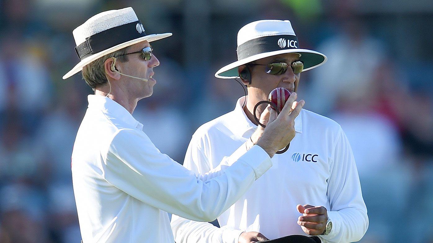 Umpire Nigel Llong inspects a ball during a Test match
