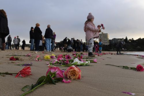 Friends and family held a vigil for Justine in Freshwater, Sydney, throwing pink flowers into the sea. Picture: AAP