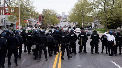 Police officers front up against protesters on the Baltimore streets. (AAP)