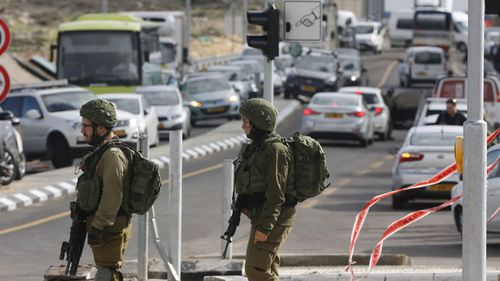 Israeli soldiers stand at the scene of an attack near the settlement of Givat Assaf in the West Bank