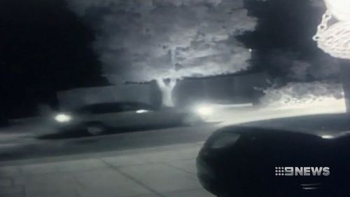 A dark-coloured late-model Holden Commodore was captured driving past and shooting into the home. (9NEWS)