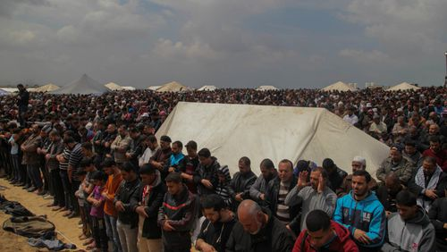 "Palestinians pray in a tent city on the Gaza border with Israel on March 30, 2018, during mass protests along the border of the Palestinian enclave, dubbed ""The Great March of Return,"" which has the backing of Gaza's Islamist rulers Hamas. (CrowdSpark/AAP)"