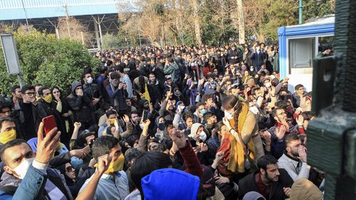 University students attend a protest inside Tehran University while anti-riot Iranian police prevent them to join other protestors. (AAP)