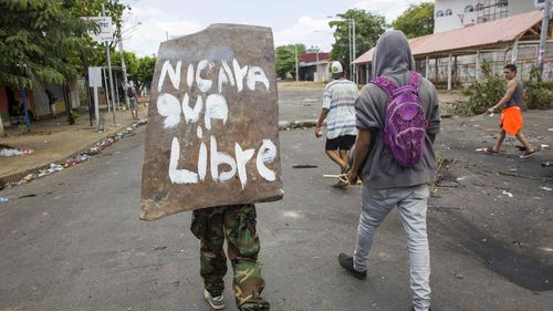 A young woman walks with a shield on his back with a message that reads 'Nicaragua Free' during the fifth day of protests in Managua, Nicaragua. (AAP)