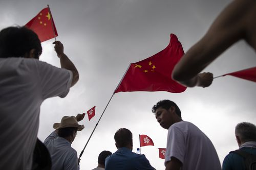Chinese national flags being waved by pro police demonstrators during the rally in support of the police.