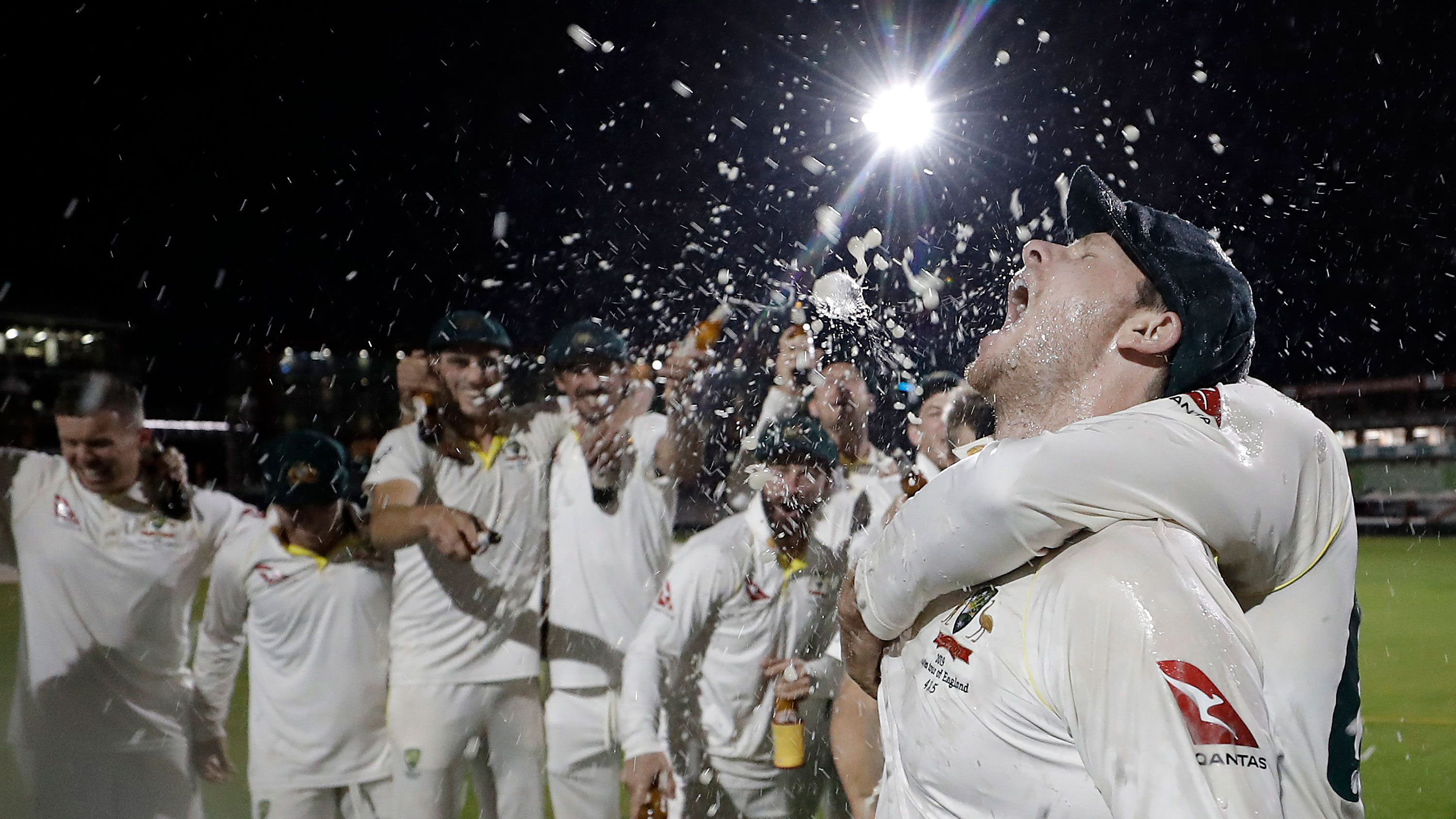 Steve Smith celebrates with his teammates while singing the team song on the pitch following victory in the fourth Test.