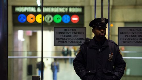 A police officer stands outside Bellevue Hospital, where Dr Spencer has been taken for treatment. (Getty)