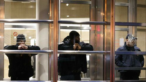 Police stand guard in the doorway of the courthouse where Joaquin 'El Chapo' Guzman is on trial.