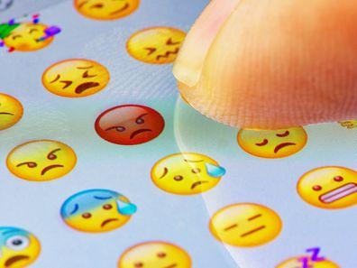 Finger touching emojis on screen.