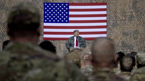 In this December 26, 2018, file photo, President Donald Trump speaks to members of the military at a hangar rally at Ain al-Asad air base, Iraq.