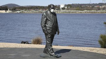 A statue of former Prime Minister Sir Robert Menzies seen wearing a face mask, along Lake Burley Griffin in Canberra.