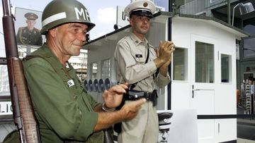 Two unidentified Germans dressed like US-Military Police pose during the openig ceremony in front of an original copy of the first border control house at the Checkpoint Charlie in Berlin Sunday, August 13, 2000.