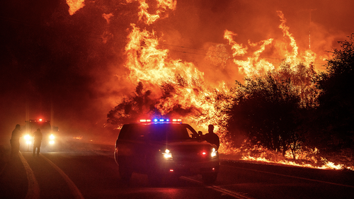 Flames lick above vehicles on Highway 162 as the Bear Fire burns in Oroville, Calif., on Wednesday, Sept. 9, 2020. (AP Photo/Noah Berger)