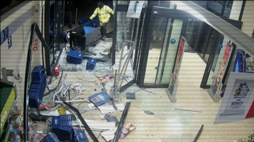 The men eventually drag the cash machine through the shattered doors.