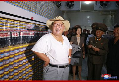 As Kim was shown around the facilities, the heat appeared to get to the leader.<br /> <br /> In what could very well be a first, Kim removed his jacket and was seen strolling around his undershirt and trousers.