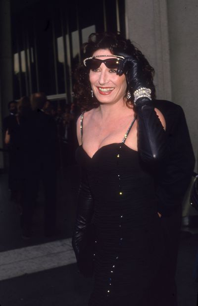 Anjelica Huston pulls off sunglasses on the red carpet at the 1987 Academy Awards.