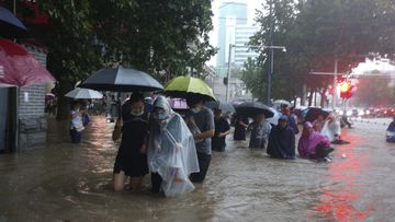 People move through flood water after a heavy downpour in Zhengzhou city, central China's Henan province.