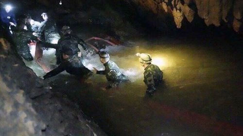 Resscuers had to wade through murky waters to find the missing children. Picture: AP