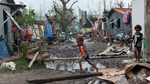 Children play amidst rubble in a street after Cyclone Pam hit Vanuatu island, South Pacific region. (AAP)