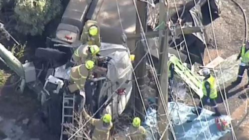 Firefighters worked for over an hour to free the driver. (9NEWS)