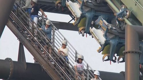 The last passenger had to wait for two hours before being brought to safety. (NHK / AP)
